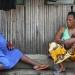 Yolande mit Schweste und Kindern, vor Wellblechhütte, Zongo
